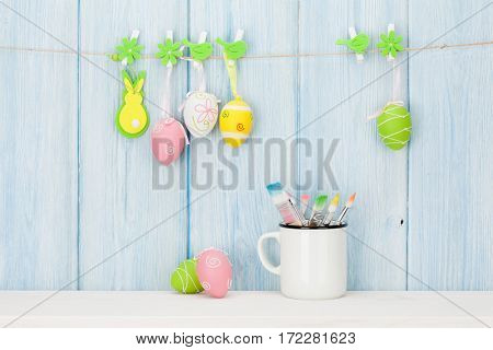Colorful easter eggs and paintbrushes in front of wooden wall