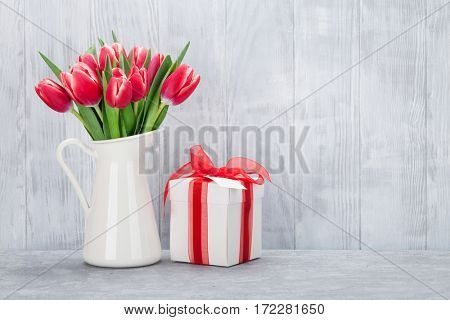 Red tulips bouquet and gift box in front of wooden wall. With space for your text