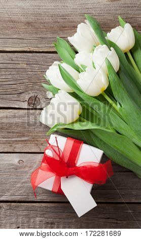 White tulips bouquet and gift box on wooden background. Top view with space for your greetings