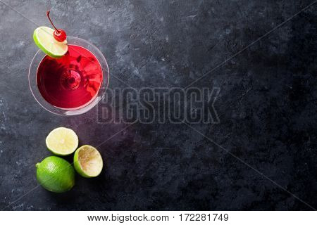 Cosmopolitan cocktail on dark stone table. Top view with space for your text