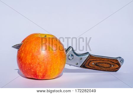 appetizing apple with a sharp knife in the middle