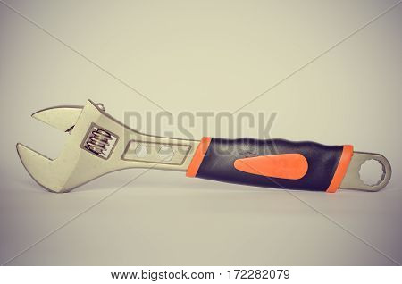 large metal wrench with rubber handle on a white background