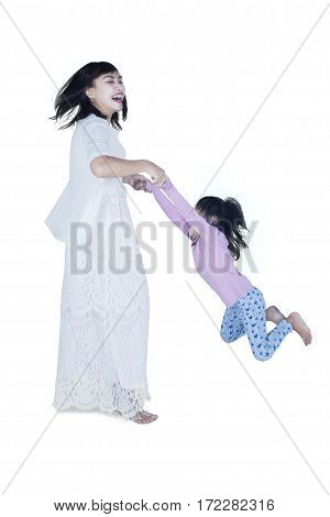 Cheerful young mother spinning her daughter in the studio isolated on white background