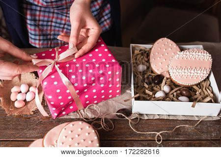 Packing sweet Easter handmade present. Unrecognizable woman preparing gift box with egg form cookies, closeup. Holiday, handmade, surprise, traditional treat concept