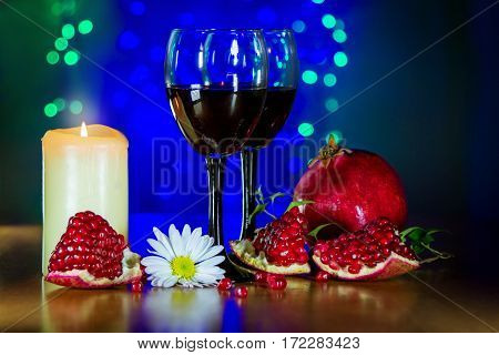 Glass of red wine, ripe pomegranate, white flower, and burning candle on the table with blurred green and blue lights on background