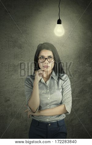 Image of pensive businesswoman thinking about something with a glowing bulb above head