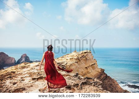 Girl in red dress among rocks and cliffs along the Coast of Algarve.