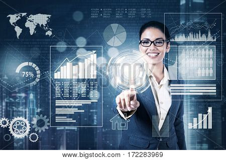 Photo of businesswoman wearing glasses and pressing digital button on the virtual screen with financial statistics