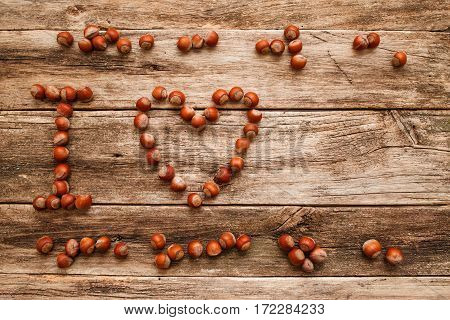 Note I Love made from hazelnuts on wood void. Top view on shabby wooden table with massage text and heart by nuts, free space for any object you want.