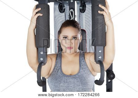Picture of strong obese female looking at the camera while workout on a shoulder press machine in the studio