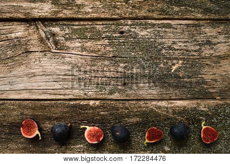 Old wooden table with figs line flat lay. Top view on empty mossy wood wit cut and full ripe purple fruits in down, free space for text or advertisement. Autumn, time, harvest concept