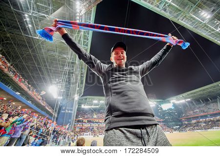 MOSCOW, RUSSIA - SEP 9, 2016: Fan (with model release) with red-and-blue scarf with CSKA MOSKOW inscription at new CSKA Arena sports complex stadium during match between CSKA and Terek soccer teams.