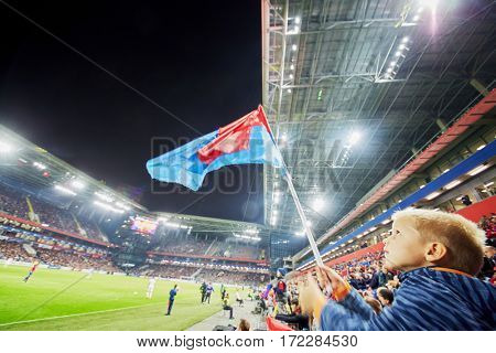 MOSCOW, RUSSIA - SEP 9, 2016: Little fan (with model release) with red-and-blue flag at new CSKA Arena sports complex stadium during match between CSKA and Terek soccer teams.
