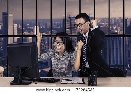 Two successful employees looking at a computer monitor on the table while expressing their achievement in the office
