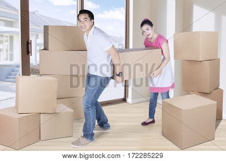 Portrait of beautiful woman and man carrying box together while moving to new home