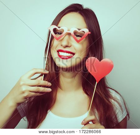 Party image. Playful young woman holding a party heart. Special fashion color processing.