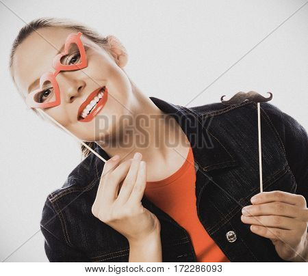 Attractive playful young woman holding mustache and glasses on a stick. Ready for party. Special fashion color processing.