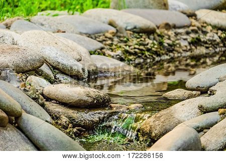 Creek in the stone bed. Pure stream flowing in the gravels and boulders. Background with limited depth of field.