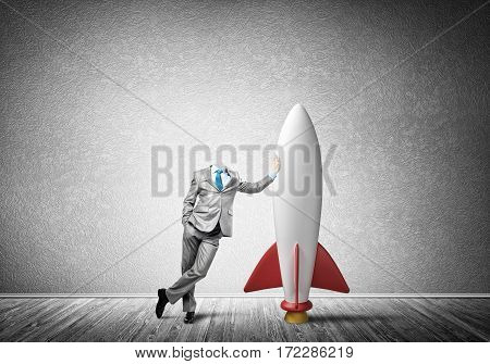Headless businessman in empty room leaning on rocket