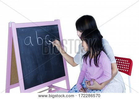 Young woman teaching alphabet to her daughter while writing letter with a chalk on blackboard