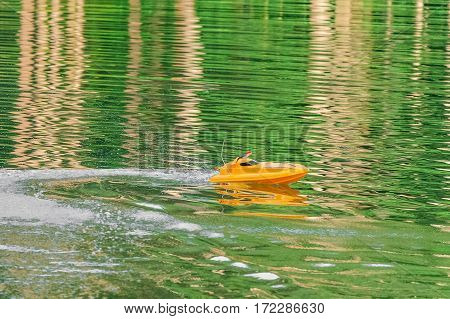 Remote controlled yellow speedboat racing after reversal