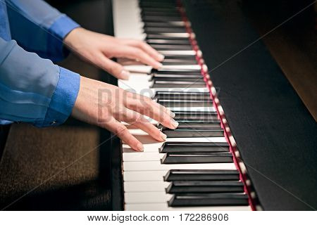 female hands in blue shirt playing the piano