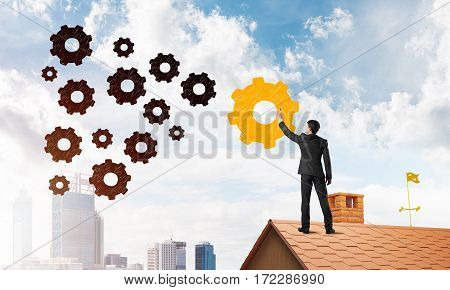 Young businessman on house top draw human resources teamwork and leadership concept. Mixed media