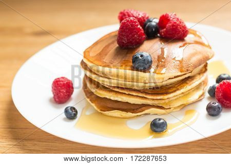 Breakfast. Berries. Pancakes. Romantic breakfast on a wooden table. Spring morning. Cozy.