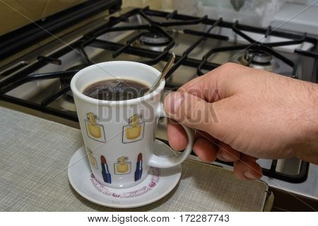 Hand with full cup of morning dose of instant coffee