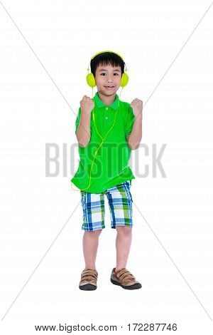 Full body of happy asian child relaxing with headphones. Isolated on white background. Smiling boy listening and enjoying music using earphone. Studio shot. Technology and music concept