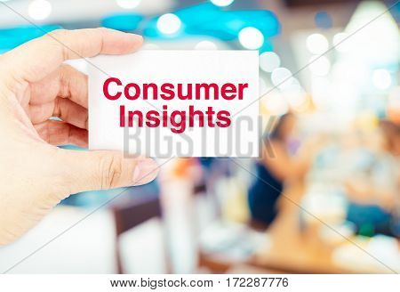 Hand Holding Business Card With Consumer Insights Word With Blur Customer At Store Background,busine