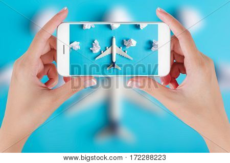 Woman hand using smart phone taking photo for preparation traveling with Airplane model flying among paper clouds. Travel concepts Ambient blurry background.