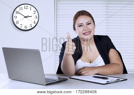 Portrait of young worker shows ok gesture and looks confident while sitting in the office