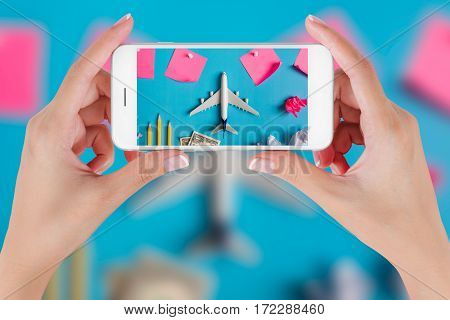Woman hand using smart phone taking photo for preparation traveling with Blank paper noted airplane money pencils paper ball and push pin. Travel concepts Ambient blurry background.