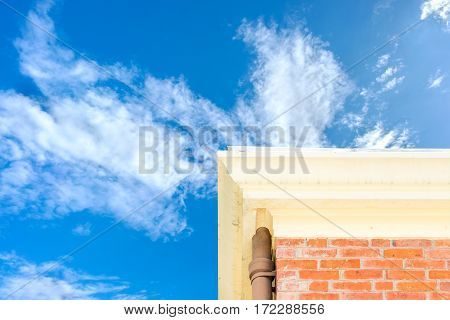 Looking up at brick house with blue sky.