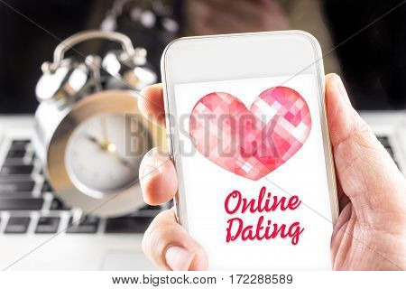 Hand Holding Mobile With Red Heart And Online Dating Word On Screen With Clock And Laptop At Backgro