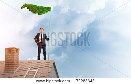 Businessman standing on house roof and holding green flag. Mixed media