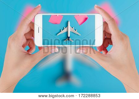 Woman hand using smart phone taking photo for preparation traveling with Blank paper noted and airplane. Travel concepts Ambient blurry background.