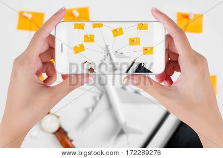 Woman hand using smart phone taking photo for preparation traveling with push pin pencil watch ear phone string and paper noted. Travel concepts Ambient blurry background.