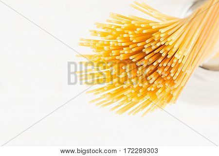 Sheaf Italian long yellow spaghetti closeup on white background.