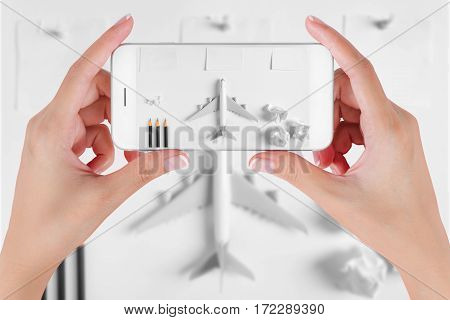 Woman hand using smart phone taking photo for preparation traveling with blank paper noted paper ball airplane push pin pencils. Travel concepts and to do list Ambient blurry background.