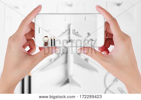 Woman hand using smart phone taking photo for preparation traveling with watch airplane pencils paper noted earphone push pin. Travel concept ambient blurry background.