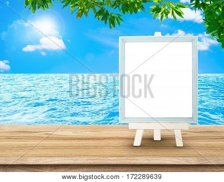 Blue Menu Board With Easel On Wood Table At Sea With Tree And Sun Burst, Copy Space For Adding Your