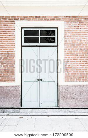 Close door at brick wall of house.