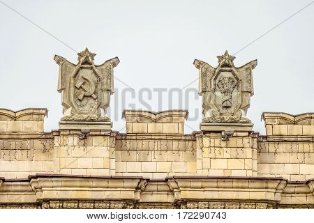 Fragment of parapet administrative government building with USSR symbols . Posters with the hammer and sickle spikelets bunch. Ornament of the Stalinist Empire style of architecture.
