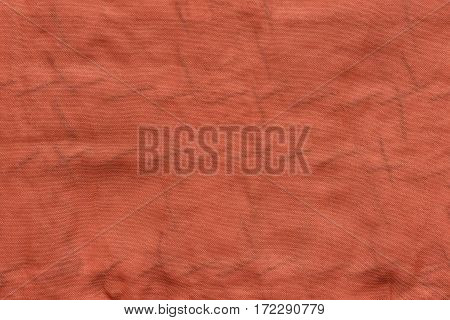 the textured background of old fabric or textile material of red color