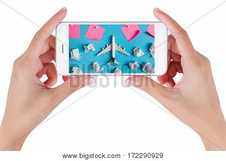 Woman hand using smart phone searching Preparation for Traveling with Airplane model flying among paper clouds and pink paper noted. Travel concepts Isolated on white background.