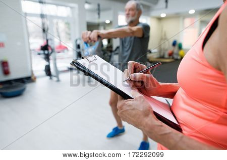 Fit senior man in sports clothing in gym working out with kettlebell. Unrecognizable personal trainer writing his progress on clipboard.