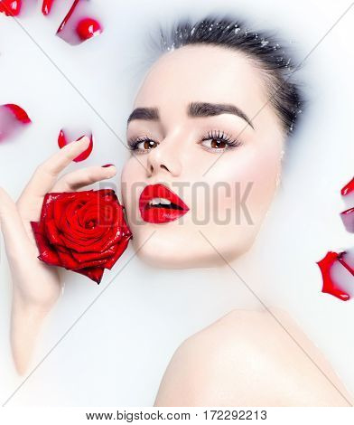 High Fashion model girl portrait taking milk bath, spa and skin care concept. Beauty young Woman with bright makeup and red rose flower relaxing in milk bath.