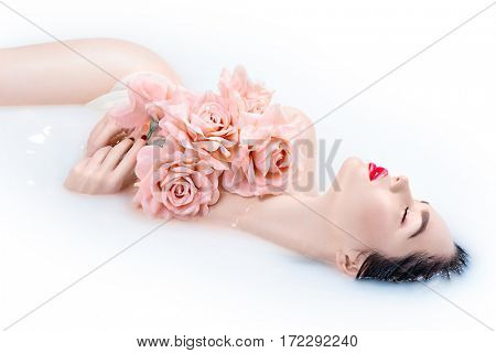 Beautiful Fashion model girl in milk bath, spa and skin care concept. Beauty young Woman with bright makeup and pink rose flowers relaxing in milk bath. Rejuvenation, skin pampering, treatment